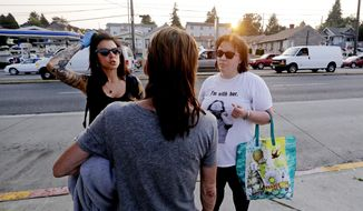 In this Aug. 9, 2018, photo, Safe Night Access Project in Seattle volunteers Justice Rivera, left, and Laura LeMoon talk with a woman while providing harm reduction services to sex workers along a north Seattle strip known for prostitution. LeMoon co-founded Safe Night Access Project in Seattle to provide harm reduction services to sex workers on the streets. She said she has seen far more women on Seattle's strolls. Solicitors have gotten younger, too, she said. She used to primarily serve middle-aged sex workers, she said, but now they often appear 25 or younger. (AP Photo/Elaine Thompson)