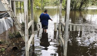 Shawn Lowrimore, son of Pastor Willie Lowrimore of The Fellowship With Jesus Ministries, wades into water near the church in Yauhannah, S.C., on Monday, Sept. 24, 2018. The church is on the bank of the Waccamaw River, which has already risen above its record crest and is expected to keep rising for several days, forcing thousands of evacuations in the aftermath of Hurricane Florence. (AP Photo/Jeffrey S. Collins)
