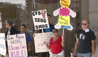 Linda Dunn, center, and Ron Freund, right, protest before the first of three public hearings on the Trump administration's proposal to roll back car-mileage standards in a region with some of the nation's worst air pollution Monday, Sept. 24, 2018 in Fresno, Calif. The day-long session by the U.S. Environmental Protection Agency and National Highway Traffic Safety Administration is a means to gather public comment concerning the mileage plan, which would freeze U.S. mileage standards at levels mandated by the Obama administration for 2020, instead of letting them rise to 36 miles per gallon by 2025. (AP Photo/Gary Kazanjian)