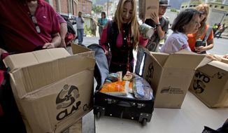 "In this July 6, 2018 photo, employees of a government-supported cultural center receive boxes with subsided food distributed under a government program named ""CLAP"" in downtown Caracas, Venezuela. Some workers transfer the contents, cooking oil, flour, rice, canned tuna, to suitcases or backpacks for fear of becoming walking targets. (AP Photo/Fernando Llano)"