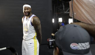 Golden State Warriors' DeMarcus Cousins, left, smiles while posing for photos for a news photographer during media day at the NBA basketball team's practice facility in Oakland, Calif., Monday, Sept. 24, 2018. (AP Photo/Jeff Chiu)