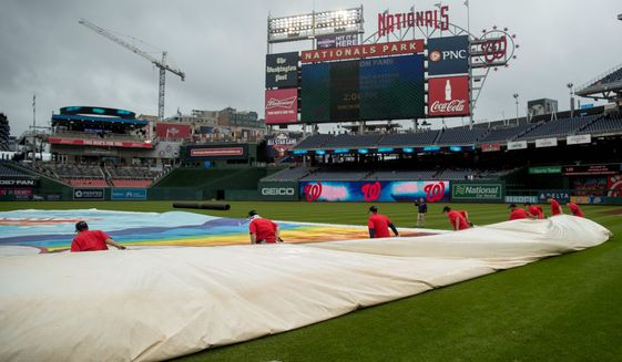Grounds crew members put the tarp on the Nationals Park field on Sunday. Major League Baseball has had the most postponements since 1997. (ASSOCIATED PRESS) ** FILE **