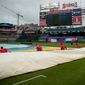 Grounds crew members put the tarp on the Nationals Park field on Sunday. Major League Baseball has had the most postponements since 1997. (ASSOCIATED PRESS)