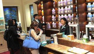 A customer sniffs tea at Fortnum & Mason in central London, a supplier of tea to Buckingham Palace, in this Sept. 14, 2018, photo. (Benjamin Plackett/Special to The Washington Times)
