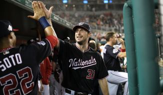 Washington Nationals starting pitcher Max Scherzer (31) gets a high five from Juan Soto (22) in the dugout during the middle of the seventh inning of a baseball game against the Miami Marlins, Tuesday, Sept. 25, 2018, in Washington. Max Scherzer recorded his 300th strikeout of the season during the seventh. (AP Photo/Nick Wass)