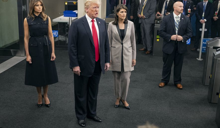 President Donald Trump addresses members of the news media as he arrives with First lady Melania Trump, left, and Nikki Haley, the U.S. ambassador to the UN, during the 73rd session of the United Nations General Assembly, at U.N. headquarters, Tuesday, Sept. 25, 2018. (AP Photo/Craig Ruttle)
