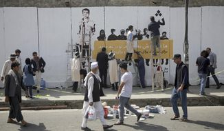 Artists from ArtLords organization, paint a mural of journalists who have been killed during the year of 2018, in Kabul, Afghanistan, Tuesday, Sept. 25, 2018. It's the first in a series of murals planned by Amnesty International and the Artlords collective to highlight the work of Afghan activists, teachers, lawyers, students, trade unionists and others. (AP Photo/Massoud Hossaini)