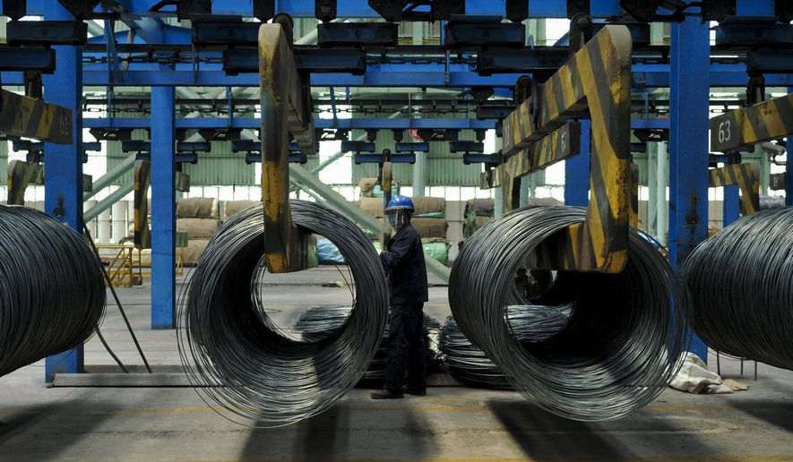 FILE - In this June 8, 2018, file photo, a worker transfers steel cables at a steel factory in Qingdao in east China's Shandong province. The Asian Development Bank has slightly downgraded its growth forecasts in its latest outlook report for the region, citing the fallout from trade tensions, rising debt and the potential impact from tightening of credit in the U.S. (Chinatopix via AP, File)