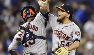 Houston Astros relief pitcher Roberto Osuna (54) celebrates with catcher Martin Maldonado (15) after the Astros defeated the Toronto Blue Jays in a baseball game Tuesday, Sept. 25, 2018, in Toronto. (Frank Gunn/The Canadian Press via AP)