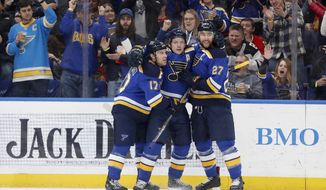 FILE - In this April 4, 2018, file photo, St. Louis Blues' Vladimir Tarasenko, of Russia, is congratulated by teammates Jaden Schwartz (17) and Alex Pietrangelo (27) after scoring during the second period of an NHL hockey game against the Chicago Blackhawks, in St. Louis. The Blues begion their season on Oct. at home against Winnipeg. (AP Photo/Jeff Roberson, File)