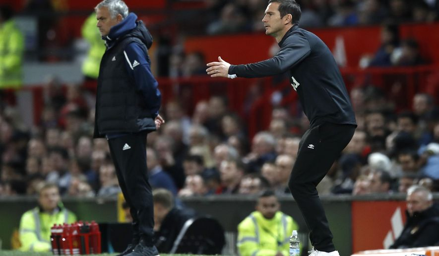 Derby County manager Frank Lampard gestures on the touchline with Manchester United manager Jose Mourinho, left, during their English League Cup, third round soccer match at Old Trafford in Manchester, England, Tuesday Sept. 25, 2018. (Martin Rickett/PA via AP)
