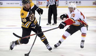 David Pastrnak (88) of the Boston Bruins takes a shot on goal past Derek Ryan (10) of the Calgary Flames during the second period of their 2018 NHL China Games hockey game in Beijing, China, Wednesday, Sept. 19, 2018. Boston beat Calgary, 3-1. (AP Photo/Mark Schiefelbein)