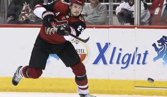 FILE - In this Dec. 2, 2017, file photo, Arizona Coyotes' Oliver Ekman-Larsson shoots the puck against the New Jersey Devils during the second period of an NHL hockey game, in Glendale, Ariz.  (AP Photo/Ralph Freso, File)