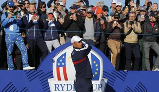 Spectators watch above as Tiger Woods of the US plays from the 1st tee during practice at Le Golf National in Guyancourt, outside Paris, France, Tuesday, Sept. 25, 2018. The 42nd Ryder Cup will be held in France from Sept. 28-30, 2018 at Le Golf National. (AP Photo/Francois Mori)