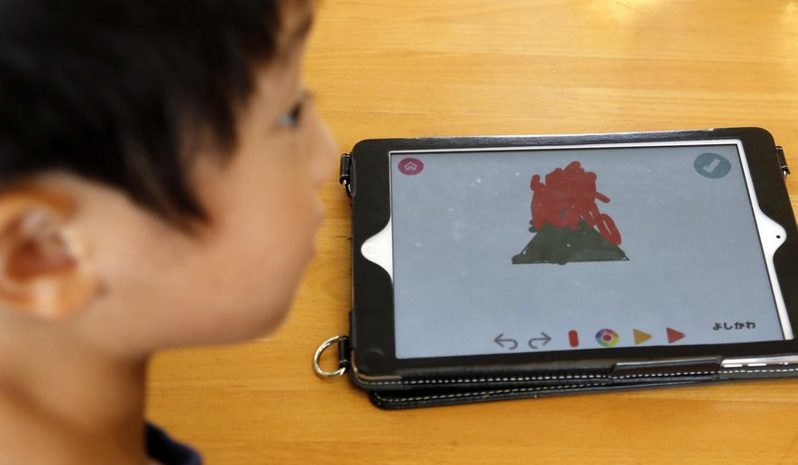 In this July 12, 2018, photo, a child works on a digital program at Coby Preschool in Yoshikawa, suburban Tokyo, on an assignment, which was to draw on a triangle on an iPad. For the kids, it's all about having fun. Japanese preschool programs equipped with tablet computers aim to prepare kids for the digital age. (AP Photo/Yuri Kageyama) ** FILE **