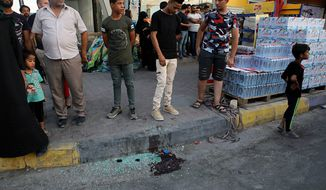People gather at the scene of the assassination of Iraqi activist Soad al-Ali, who has been involved in organizing protests demanding better services in the city, in the southern city of Basra, Iraq, Tuesday, Sept. 25, 2018. A police official said masked gunmen shot dead al-Ali, a mother of four, outside a supermarket. The gunmen fled the scene after shooting at her and her husband in their car. (AP Photo/Nabil al-Jurani)