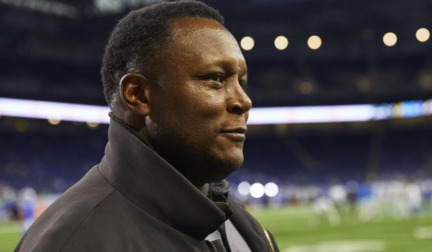 FILE - In this Monday, Sept. 10, 2018, file photo, former Detroit Lions Hall of Fame running back Barry Sanders smiles on the sidelines before an NFL football game against the New York Jets in Detroit. Sanders will join the Detroit Lions for their next game in Dallas, on Sunday, Sept. 30, as an ambassador for a team he left behind with a sudden retirement that created a rift between him and the franchise and fans. (AP Photo/Rick Osentoski, File)