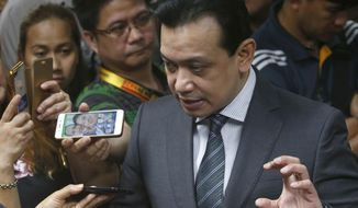 Philippine opposition Sen. Antonio Trillanes IV talks to the media outside his office in the Philippine Senate following a regional trial court order for his arrest Tuesday, Sept. 25, 2018 in suburban Pasay city, south of Manila, Philippines. Trillanes who remained holed up in his office for three weeks now after President Rodrigo Duterte voided an amnesty given to the former rebel military officer, willingly went with police to post bail. (AP Photo/Bullit Marquez)