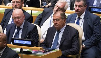 Russian Foreign Minister Sergey Lavrov, right, and Ambassador to the United Nations Vassily Nebenzia, center, listen as American President Donald Trump addresses the 73rd session of the United Nations General Assembly, Tuesday, Sept. 25, 2018 at U.N. headquarters. (AP Photo/Mary Altaffer)