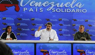 In this photo released by the Miraflores Press Office, Venezuela's President Nicolas Maduro, center, speaks, as he is accompanied by Venezuela's Vice President Delcy Rodriguez, left, and Defense Minister Vladimir Padrino, right, during a meeting with Colombian citizens that reside in Venezuela, In Caracas, Venezuela, Tuesday, Sept. 25, 2018. The Trump administration has slapped financial sanctions on four members of Venezuelan President Nicolas Maduro's inner circle, including his wife and the nation's vice president, on allegations of corruption. (AP Photo/HO)
