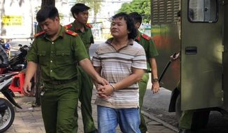 In this Monday, Sept. 24, 2018, photo, Vietnamese activist Doan Khanh Vinh Quang, front right, is escorted to the court house in Can Tho province, Vietnam. Quang was sentenced to 27 months in prison for his Facebook posts that judges say insulted the ruling Communist Party and government and called for anti-government protests. (Thanh Sang/Vietnam News Agency via AP)