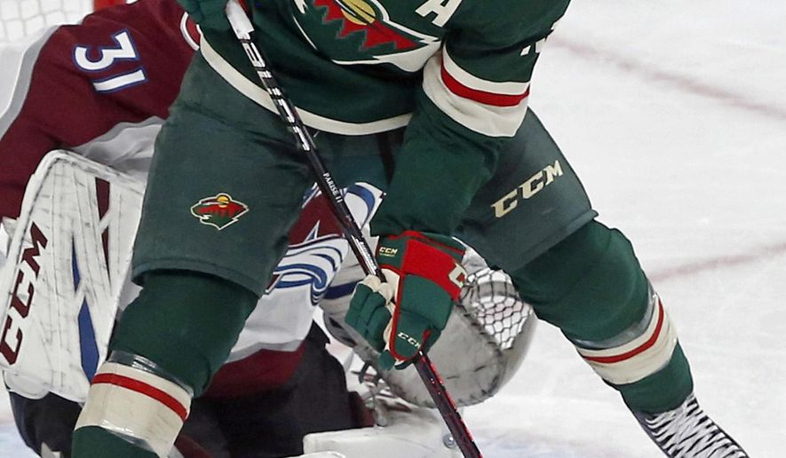 FILE - In this Sept. 22, 2018, file photo, Minnesota Wild's Zach Parise (11) jumps to clear the way for a shot against Colorado Avalanche's goalie Philipp Grubauer during an NHL preseason hockey game in St. Paul, Minn. The team is banking on rebounds by several key players, including a healthy Parise and Ryan Suter. (AP Photo/Jim Mone, File)