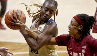 FILE - In this Feb. 4, 2018 file photo Pittsburgh's Yacine Diop, left, maintains control of a rebound as Florida State's Nicole Ekhomu reaches for the ball during the second half of an NCAA college basketball game in Pittsburgh. Several college players are getting quite the education on the court playing against the best players at the FIBA Women's Basketball World Cup. All of them hope to bring their experiences back to school next week when they return to campuses across the U.S. Diop has a great story to tell her new teammates at Louisville. She is headed their as a graduate transfer as playing at Pitt. Diop helped Senegal beat Latvia on Sunday and advance out of pool play for the first time in the country's history. In fact it was the first time in FIBA history that an African team won a preliminary round game. (AP Photo/Keith Srakocic, file)