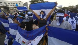 Anti-government protesters march outside the Central American University (UCA) in Managua, Nicaragua, Wednesday, Sept. 26, 2018, before police blocked the march from reaching its planned destination, the local U.N. headquarters. More than 300 people are estimated to have been killed since April in months of anti-government protests and harsh government crackdown. (AP Photo/Alfredo Zuniga)