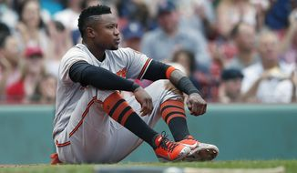 Baltimore Orioles' Tim Beckham sits behind home plate after being thrown out trying to score on a double by Joey Rickard during the third inning of the first game of a baseball double header against the Boston Red Sox in Boston, Wednesday, Sept. 26, 2018. (AP Photo/Michael Dwyer) ** FILE **