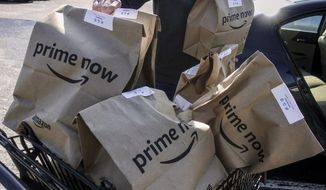 FILE - In this Feb. 8, 2018, file photo, Amazon Prime Now bags full of groceries are loaded for delivery by a part-time worker outside a Whole Foods store in Cincinnati. Amazon and Whole Foods are rolling out their grocery delivery service in several locations Wednesday, Sept. 26, while expanding it in other areas. (AP Photo/John Minchillo, File)