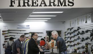 FILE - In this Dec. 9, 2015, file photo, sales associate Mike Conway, right, shows Paul Angulo a pistol at Bullseye Sport gun shop in Riverside, Calif. Gov. Jerry Brown has signed a new law requiring that Californians undergo at least eight hours of training, including live fire exercises, before carrying concealed weapons. (AP Photo/Jae C. Hong, File)