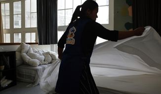 In this Thursday, Sept. 20, 2018 photo, a cleaning lady works in an apartment located on Airbnb in Paris. The spectacular growth of Airbnb in Paris, the top worldwide location for the internet giant is also raising alarms in the French capital. Some Parisians and officials at City Hall blame the site for driving Parisian families out of the city center, leading to school closures and concerns that the French capital is losing its life and charms. (AP Photo/Thibault Camus)