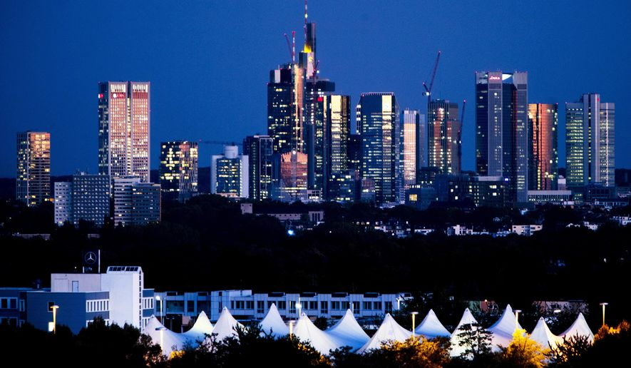 The buildings of the banking district are illuminated by red clouds after sunset in Frankfurt, Germany, Tuesday, Sept. 25, 2018. (AP Photo/Michael Probst)