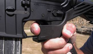"""In this Oct. 4, 2017, file photo, a shooting instructor demonstrates the grip on an AR-15 rifle fitted with a """"bump stock"""" at a gun club in North Carolina. (AP Photo/Allen G. Breed, File)"""