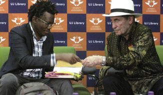South African lawyer Tembeka Ngcukaitobi, left, and former South African judge Albie Sachs sit together during a speaking event on Tuesday, Sept. 25, 2018, at the University of Johannesburg. The two men discussed anti-apartheid leader Nelson Mandela, who was honored at the United Nations this week with the unveiling of a statue. (AP Photo/Christopher Torchia)