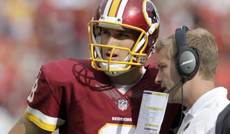 FILE - In this Sept. 14, 2014, file photo, then-Washington Redskins quarterback Kirk Cousins (8) listens to then-offensive coordinator Sean McVay during the second half of an NFL football game against the Jacksonville Jaguars, in Landover, Md.  Cousins might not be an $84 million quarterback if McVay hadn't masterminded his development in Washington. The student meets the teacher Thursday, Sept. 27, 2018, when the Minnesota Vikings and the Los Angeles Rams attempt to overcome their injury woes in a short-week NFC showdown. (AP Photo/Mark E. Tenally, File)