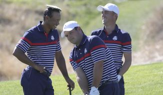 Tiger Woods of the US places the cover of a water sprinkler as he jokes with Patrick Reed, center, and Jordan Spieth, right, during a practice round of the Ryder Cup at Le Golf National in Saint-Quentin-en-Yvelines, outside Paris, France, Thursday, Sept. 27, 2018. The 42nd Ryder Cup will be held in France from Sept. 28-30, 2018 at Le Golf National. (AP Photo/Francois Mori)