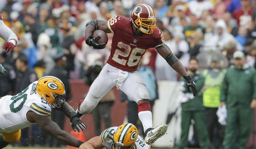 FILE - In this Sept. 23, 2018, file photo, Washington Redskins running back Adrian Peterson (26) leaps over Green Bay Packers linebacker Kyler Fackrell (51) during the second half of an NFL football game, in Landover, Md. Peterson is confirming to everyone else in the NFL he's still got it. His 236 yards are good for fifth in the league, only three players have more than his three touchdowns and the 33-year-old's contributions are one of the biggest reason the Redskins are 2-1 at their bye week. (AP Photo/Carolyn Kaster, File) **FILE**