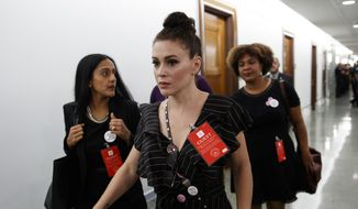 Actress Alyssa Milano walks to a Senate Judiciary Committee hearing after a break on Capitol Hill in Washington, Thursday, Sept. 27, 2018, with Christine Blasey Ford and Supreme Court nominee Brett Kavanaugh. (AP Photo/Carolyn Kaster) ** FILE **