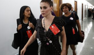 Actress Alyssa Milano walks to a Senate Judiciary Committee hearing after a break on Capitol Hill in Washington, Thursday, Sept. 27, 2018, with Christine Blasey Ford and Supreme Court nominee Brett Kavanaugh. (AP Photo/Carolyn Kaster)