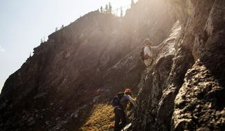 In a Tuesday, Sept. 11, 2018 photo, U.S. Navy veteran Jeff Kloppenburg picks his way up a route on Jackson Hole Mountain Resort's via ferrata in Teton Village, Wyoming, followed behind by guide Mash Alexander. The resort partnered with Teton Adaptive Sports for the group climb to celebrate veterans on September 11.  (Ryan Dorgan/Jackson Hole News & Guide via AP)