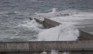 Two men try to secure boats due to bad weather at the port of Rafina, east of Athens, on Thursday, Sept. 27, 2018. Severe weather warnings remain in effect around Greece, halting ferry services and prompting school closures. (AP Photo/Thanassis Stavrakis)