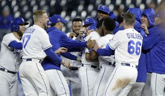 Kansas City Royals mob designated hitter Salvador Perez after he drove in the winning run during the 10th inning of a baseball game against the Cleveland Indians at Kauffman Stadium in Kansas City, Mo., Thursday, Sept. 27, 2018. The Royals defeated the Indians 2-1. (AP Photo/Orlin Wagner)