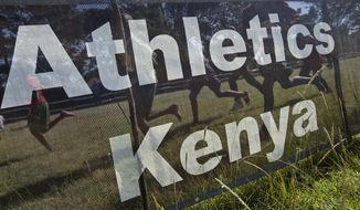 FILE - In this Sunday, Jan. 31, 2016 file photo, junior athletes run past a sign for Athletics Kenya at the Discovery cross country races, an annual race held to identify up-and-coming new young talent, in Eldoret, Kenya. Kenyan athletes are the target of nearly a quarter of all out-of-competition doping tests in track and field, a statistic that underlines how much suspicion has been cast over the most successful distance-running nation in the world. The number was revealed Thursday, Sept. 27, 2018 by the head of the Athletics Integrity Unit, which handles anti-doping for world track and field body the IAAF.(AP Photo/Ben Curtis, File)