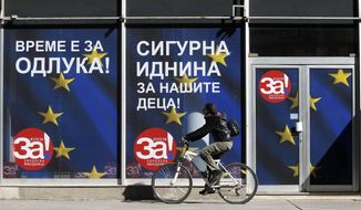 "A woman rides a bicycle next to a poster ""For European Macedonia"", on a street in Skopje, Macedonia, Thursday, Sept. 27, 2018. Macedonians will vote Sunday in a referendum on whether to change the country's name to ""North Macedonia"", a move which would allow the Balkan country to qualify for NATO membership and also pave its way toward the European Union. The banner also reads in Macedonian ""It is time for decision"" and ""A secure future for our children"". (AP Photo/Boris Grdanoski)"