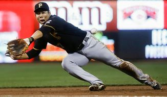 FILE - In this Friday, Sept. 16, 2016, file photo, Pittsburgh Pirates third baseman Jung Ho Kang misses a double hit by Cincinnati Reds' Adam Duvall during the first inning of a baseball game in Cincinnati. The Pirates expect Kang to join the club Friday, Sept. 28, and be active for a season-ending season at Cincinnati in what would be his first major league appearance in two years. (AP Photo/John Minchillo, File)