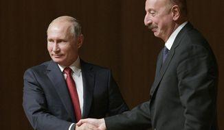 Russian President Vladimir Putin, left, and Azerbaijan's President Ilham Aliyev shake hands during their meeting in Baku, Azerbaijan, Thursday, Sept. 27, 2018. (Alexei Druzhinin, Sputnik, Kremlin Pool Photo via AP)