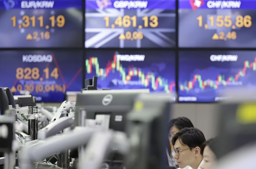 Currency traders work near screens showing the foreign exchange rates at the foreign exchange dealing room in Seoul, South Korea, Thursday, Sept. 27, 2018. Asian markets were mixed on Thursday after the U.S. Federal Reserve lifted its key interest rate as expected for the third time this year. (AP Photo/Lee Jin-man)