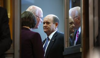 Sen. Chris Coons, D-Del., center, with Sen. Patrick Leahy, D-Vt., and Sen. Amy Klobuchar, D-Minn., left, are seen inside the anteroom during the Senate Judiciary Committee meeting, Friday, Sept. 28, 2018, on Capitol Hill in Washington. After a flurry of last-minute negotiations, the Senate Judiciary Committee advanced Brett Kavanaugh's nomination for the Supreme Court after agreeing to a late call from Sen. Jeff Flake, for a one-week investigation into sexual assault allegation against the high court nominee. (AP Photo/Pablo Martinez Monsivais)