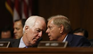 Senator John Cornyn (R-TX) and Senator Lindsey Graham (R-SC) talks as Dr. Christine Blasey Ford speaks before the Senate Judiciary Committee hearing on the nomination of Brett Kavanaugh to be an associate justice of the Supreme Court of the United States, on Capitol Hill in Washington, DC, USA, 27 September 2018. US President Donald J. Trump's nominee to be a US Supreme Court associate justice Brett Kavanaugh is in a tumultuous confirmation process as multiple women have accused Kavanaugh of sexual misconduct.  (Michael Reynolds/Pool Photo via AP)